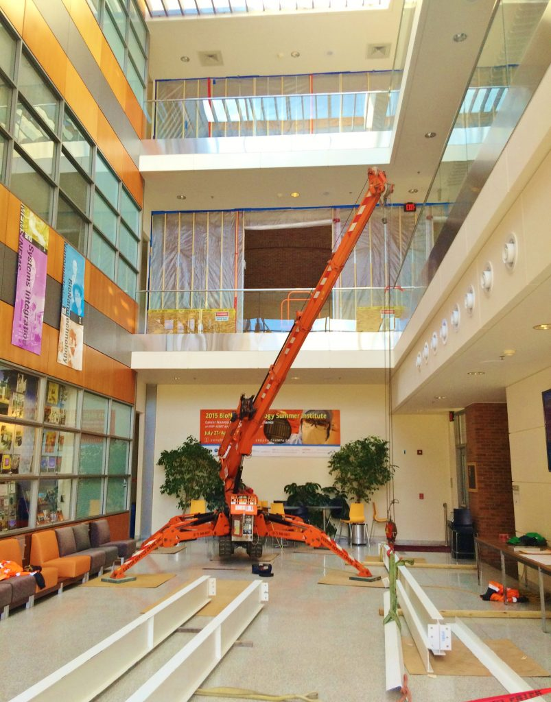 Jekko mini crane lifting beams inside an academic building.