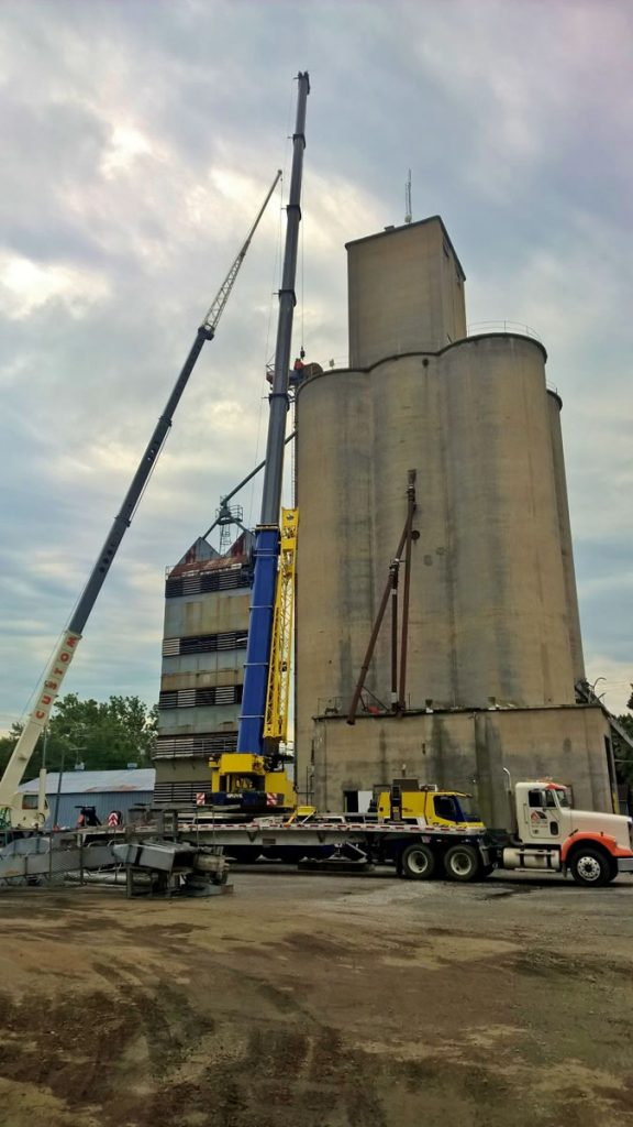 275 & 60 ton cranes tearing down rusty old leg next to concrete silos