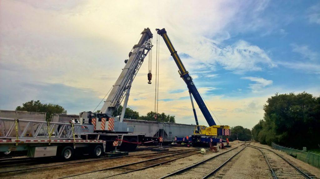two 275 ton hydraulic cranes assist a rail car