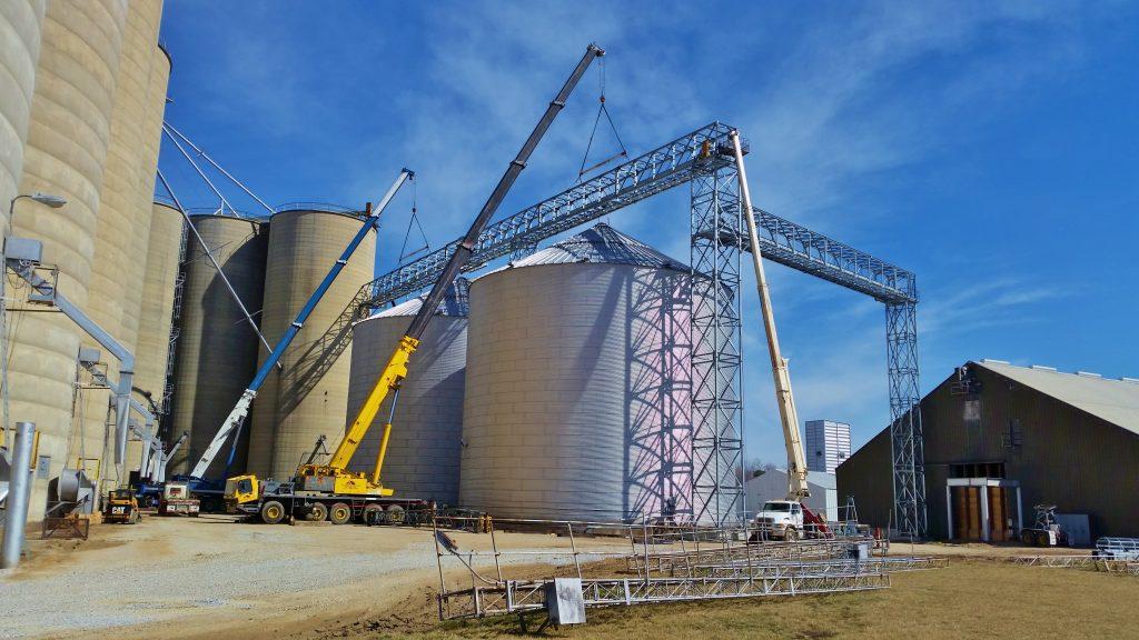 Two 175 ton hydraulic cranes lifting a bridge truss at grain bins