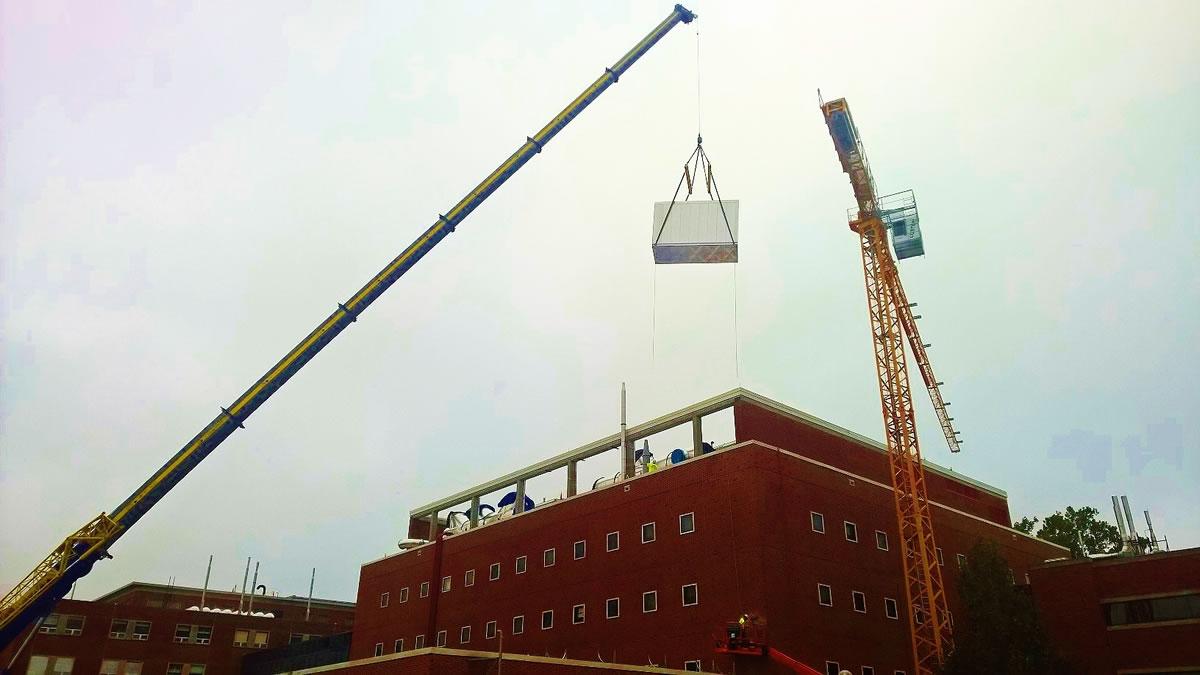 275 hydraulic crane hoisting HVAC with tower crane in background on campus in Urbana, IL