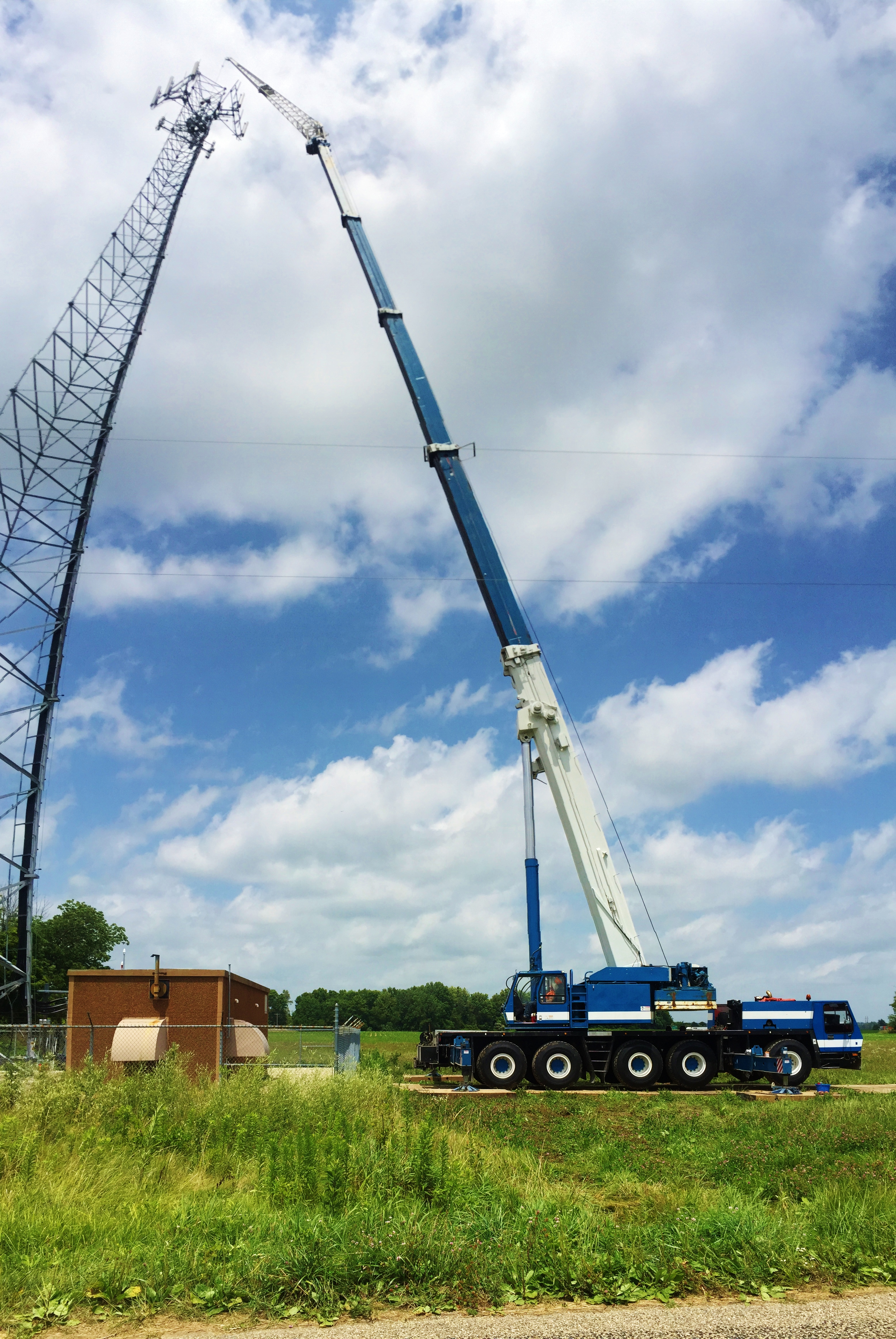 175 ton crane reaches high to hoist new antennas for a cell tower.